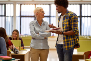 = female professor discusses lesson with black student